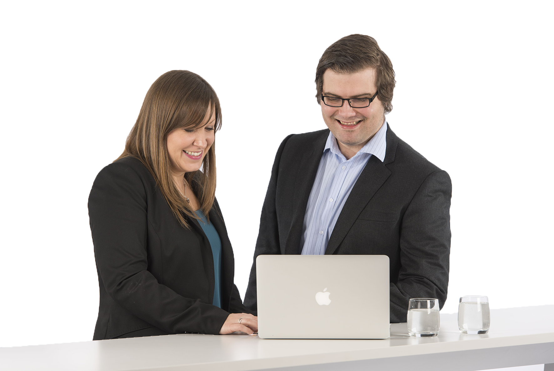 A women and a man looking at a laptop smiling and wearing smart business attire | Hugh James