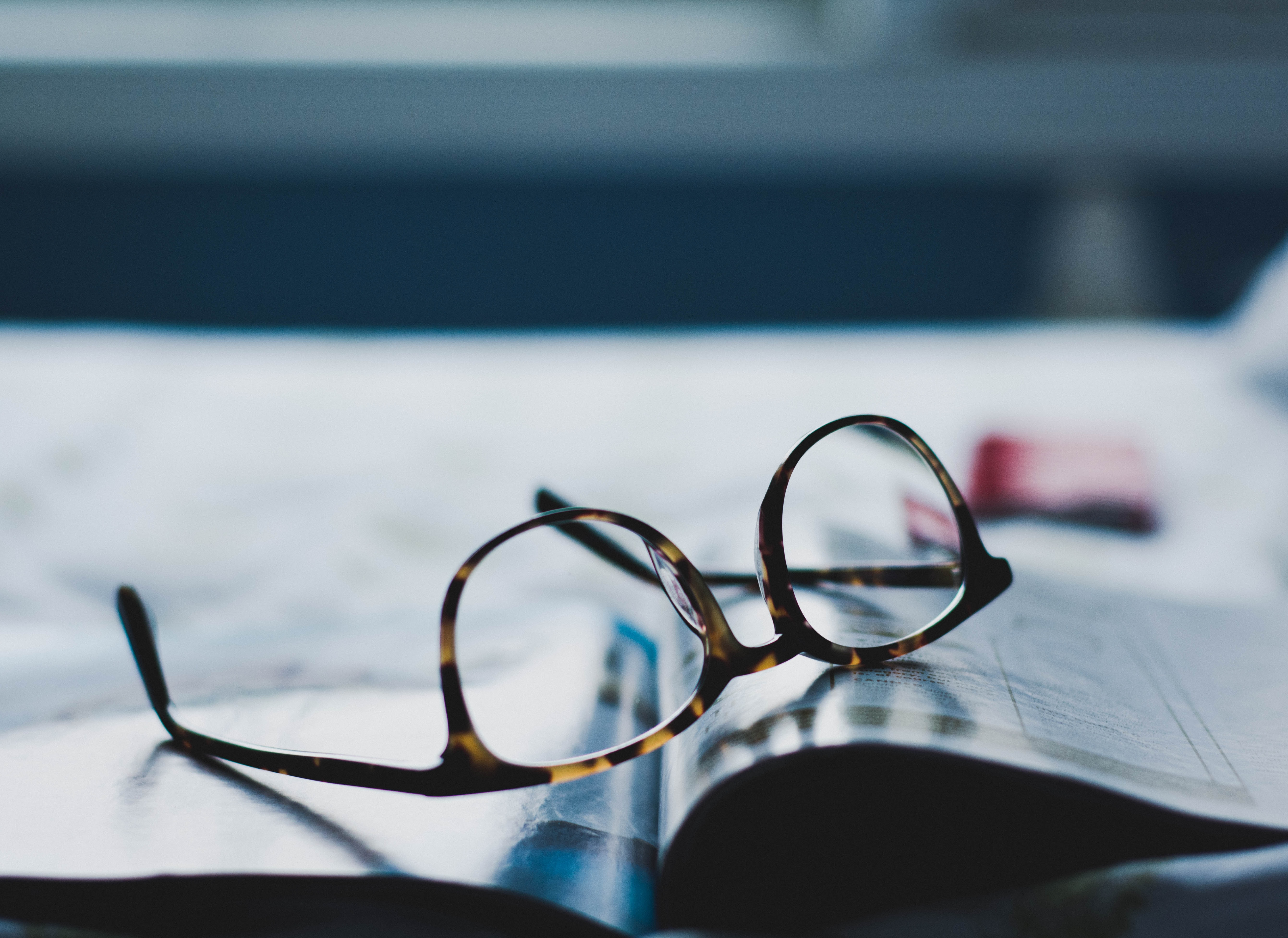 Reading glasses on top of book | Hugh James